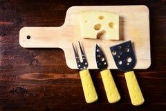 Малые ножи сыра и прерывая доска с сыром emmenthal дальше Стоковая Фотография