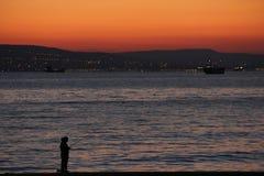 Малые рыболовы на море на заходе солнца стоковая фотография
