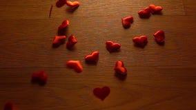 Малые сердца совмещают большую форму сердца на деревянной поверхности Супер видео замедленного движения сток-видео