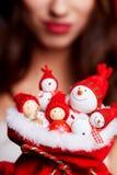 Малые снеговики в красных шляпах в сумке в руках модели Стоковые Фотографии RF