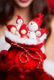 Малые снеговики в красных шляпах в сумке в руках модели Стоковое Фото