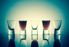 Малые стекла при съемки питья спирта stainding в таблице Стоковая Фотография