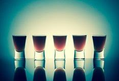 Малые стекла при съемки питья спирта stainding в таблице Стоковые Фотографии RF