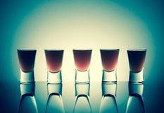 Малые стекла при съемки питья спирта stainding в таблице Стоковые Изображения RF