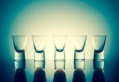 Малые стекла при съемки питья спирта stainding в таблице Стоковое Фото