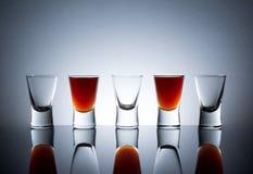 Малые стекла, съемки питья спирта с отражением Стоковые Изображения