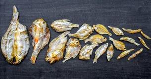 Малые сухие рыбы от солнца на черном деревянном поле Стоковое Фото