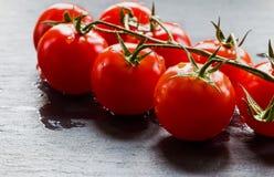 Малые томаты вишни на черной каменной предпосылке Стоковые Фотографии RF