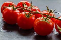 Малые томаты вишни на черной каменной предпосылке Стоковое Изображение