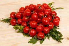 Малые томаты и свежие травы на деревянной предпосылке стоковые фотографии rf