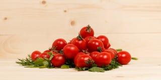 Малые томаты и свежие травы на деревянной предпосылке стоковые изображения rf