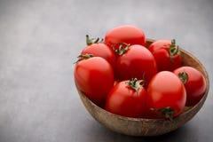 Малые томаты сливы в деревянном шаре на серой предпосылке Стоковое Изображение RF