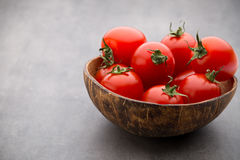Малые томаты сливы в деревянном шаре на серой предпосылке Стоковая Фотография