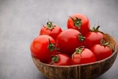 Малые томаты сливы в деревянном шаре на серой предпосылке Стоковое Изображение