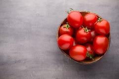 Малые томаты сливы в деревянном шаре на серой предпосылке Стоковые Изображения