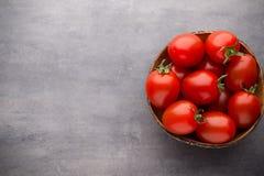 Малые томаты сливы в деревянном шаре на серой предпосылке Стоковая Фотография RF