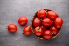 Малые томаты сливы в деревянном шаре на серой предпосылке Стоковые Изображения RF