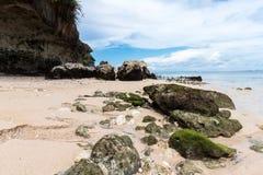 Малые утесы разбросанные на конец песка пляжа вверх Красивый ландшафт океана, изумительное небо bali Индонесия Стоковое фото RF