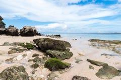 Малые утесы разбросанные на конец песка пляжа вверх Красивый ландшафт океана, изумительное небо bali Индонесия Стоковые Изображения