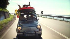 Малый автомобиль заполненный с детьми забавляется, дорога к пляжу сток-видео