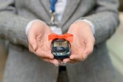 Малый автомобиль сувенира в руках saleswomans Стоковое фото RF