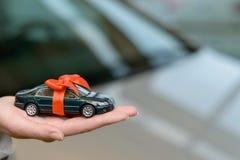Малый автомобиль сувенира на ладони продавщицы Стоковые Фотографии RF