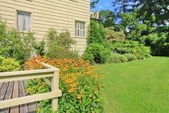 Малый американский дом с светлым экстерьером и большой травой заполнил лужайку Стоковые Изображения