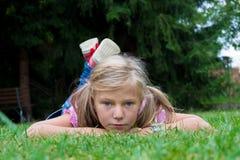 Малый белокурый ребенок девушки с ponytail кладет в траву наслаждаясь summ Стоковое Изображение