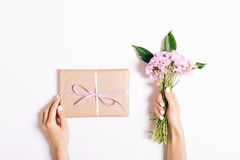 Малый букет розовых гвоздик и подарка с лентой в женщине Стоковые Изображения RF