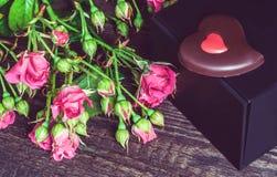 Малый букет роз и подарка на деревянной предпосылке Стоковая Фотография