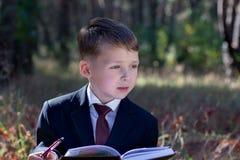 Малый воодушевленный ребенок в деловом костюме смотрит в сторону Стоковые Изображения RF