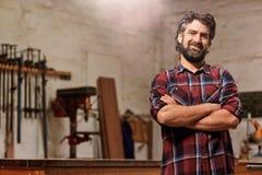Малый владелец бизнеса плотничества усмехаясь при пересеченные оружия стоковое фото