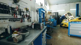 Малый гараж автомобиля - автоматический механик проверяет двигатель в клобуке желтого автомобиля сток-видео