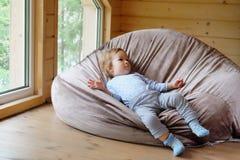 Малый европейский мальчик лежит на сумке фасоли Стоковое фото RF