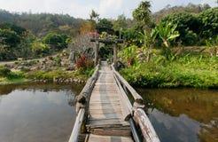 Малый деревянный мост над рекой в старой тайской деревне с деревьями вокруг Стоковое Изображение