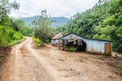 Малый деревянный дом фермы и пакостная дорога стоковая фотография
