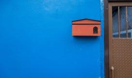 Малый красный почтовый ящик на голубом доме стены Стоковые Изображения RF