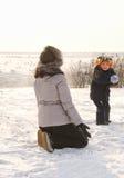 Малый мальчик бросая снежный ком на его мать Стоковая Фотография RF