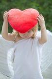 Малый мальчик в крылах ангела и сердце pillow Стоковая Фотография RF