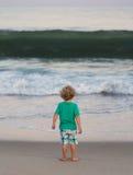 Малый мальчик наблюдая, как большая волна причалила Стоковые Изображения RF