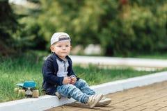 Малый мальчик сидит на предпосылке зеленого цвета нерезкости Стоковые Фото