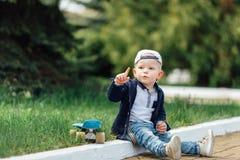 Малый мальчик сидит на предпосылке зеленого цвета нерезкости Стоковое фото RF