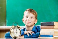 Малый мальчик сидя с будильником около классн классного Стоковое Фото
