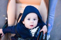Малый милый newborn ребёнок сидя в экипаже в теплой зиме одевает с pacifier, концепцией быть матерью beanie осени, прогулки t стоковые фото
