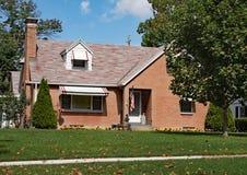 Малый дом кирпича с искусственными цветками стоковое изображение