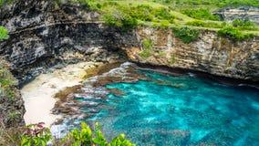 Малый песчаный пляж в переднем своде камня iof над морем Сломленный пляж Береговая линия утеса Nusa Penida, Индонезия Стоковое Изображение RF