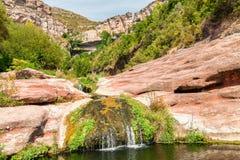 Малый поток с монастырем Сан Miquel del Fai в предпосылке, Sp Стоковые Фотографии RF