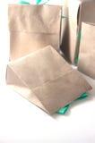 Малый подарок обернутый в рециркулированной бумаге с смычком ленты Стоковые Фотографии RF