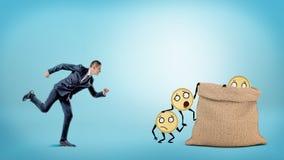 Малый предприниматель бежать к большому полному мешку куда много монеток с оружиями и ногами получают внутри Стоковое Изображение RF