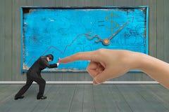 Малый предприниматель нажимая против forefinger сильной руки Стоковые Фотографии RF